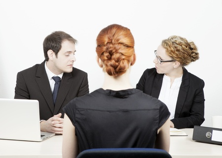 A male and female business executive conducting a job interview with a redhead woman applicant who is sitting in the foreground with her back to the camera Stock Photo