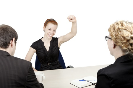 exultant: Successful female corporate job applicant rejoicing with her fist raised in the air Stock Photo