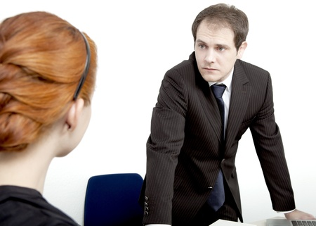 unimpressed: Rear view of a redheaded female employee confronting her male boss who is standing behind his desk looking at her with an unimpressed expression