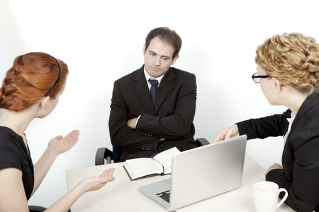 unimpressed: Two women try to explain a business proposal to an unimpressed man. Business meeting concept