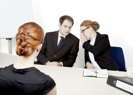 View over the shoulder of a redhead female applicant of two personnel managers conducting a job interview whispering amongst themselves about their impression and decision