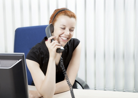 Cheerful friendly motivated young business woman sitting in her office at her desk chatting on a telephone, with copyspace photo