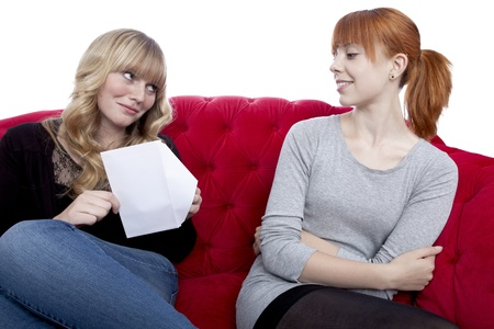 young beautiful blond and red haired girls open a letter on red sofa in front of white background photo