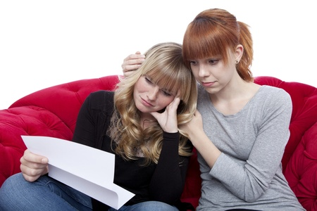 young beautiful blond and red haired girls on red sofa are sad because of bad letter in front of white background photo