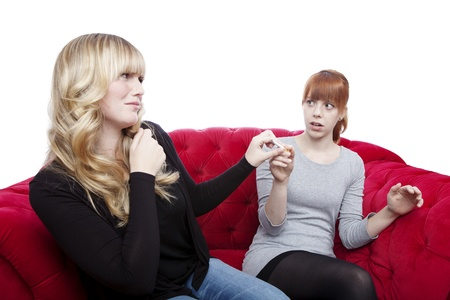 young beautiful blond and red haired girls get cigarette away on red sofa in front of white background