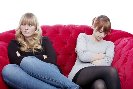 angry couple: young beautiful blond and red haired girls on red sofa have a conflict in front of white background Stock Photo