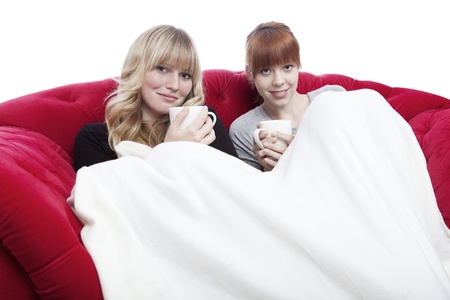 young beautiful blond and red haired girls get warm under cover on red sofa in front of white background photo