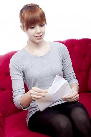 jonge mooie roodharige meisje zitten op rode sofa en een brief ontvangen in de voorkant van de witte achtergrond