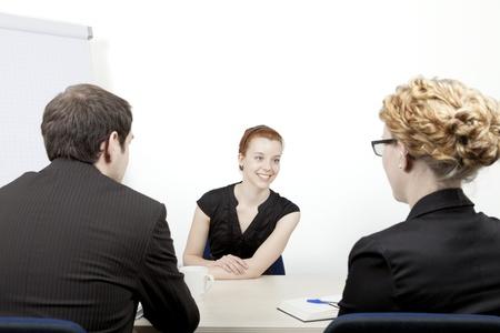 Jonge vrouw wordt geïnterviewd voor een baan glimlacht als ze beantwoordt vragen van de twee corporate interviewers, een man en een vrouw, die zitten met hun rug naar de camera