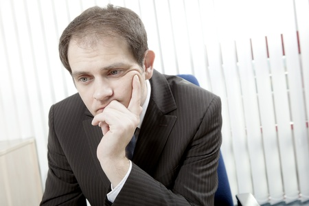 demotivated: Depressed worried businessman sitting at his desk with his chin in his hand thinking and trying to make difficult decisions
