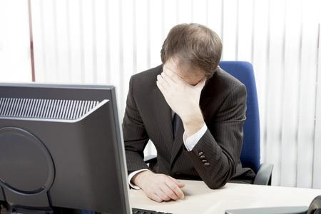 Wanhopig zakenman zittend aan zijn bureau in zijn kantoor rust zijn voorhoofd in zijn handen, waarvan hij meent de hopeloosheid van de situatie