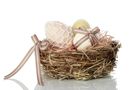 straw twig: Neat straw and twig nest full of traditional hand decorated Easter Eggs on a white studio background