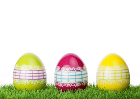 three wishes: Three colourful decorative Easter Eggs tied around with ornamental lacy ribbon standing on short green grass against a white background with copy space for your greeting