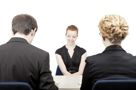 Rear view of a male and female personnel officer interviewing an attractive smiling female candidate for a vacant job position in a corporation