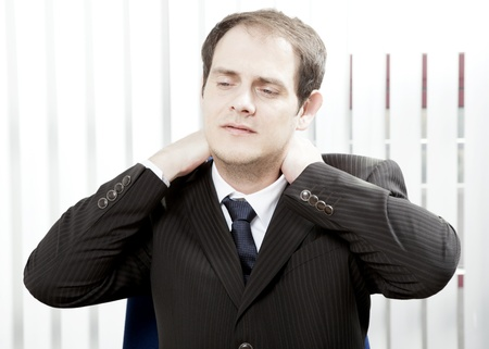 Businessman with a stiff neck or tension headache holding his hands behind his head while grimacing in pain