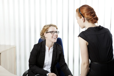 camaraderie: Two female business colleagues having a chat and laughing together as they share a private moment during an informal meeting in the office