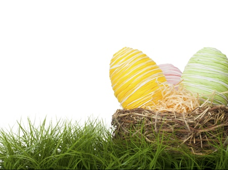 Country handcrafted Easter Eggs bound with coloured raffia straw in delicate pastel colours hidden in a straw nest on green grass for the traditional Easter Egg Hunt with copy space Standard-Bild