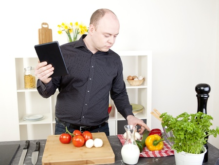 checking ingredients: Man cooking in the kitchen carefully checking his fresh ingredients, herb and vegetables while holding a tablet in his other hand