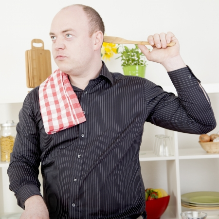 household chores: Man standing lost in thought while cooking in the kitchen absent mindedly scratching the back of his head with a wooden spoon