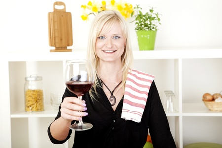 dishcloth: Elegant beautiful blonde woman standing in the kitchen with a dishcloth over her shoulder smiling and making a toast with a glass of red wine
