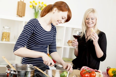 second meal: Two attractive women friends preparing a meal in the kitchen together with one chopping vegetables watched by the second who is enjoying a glass of red wine