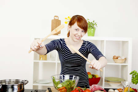 Happy smiling young redhead woman in the kitchen tossing a fresh salad with two wooden salad servers as she prepares a healthy meal photo