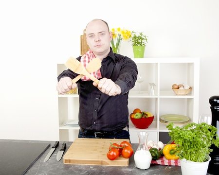 household chores: Fun image of a man preparing to start cooking a healthy vegetarian meal standing holding up the wooden salad utensils crossed in front of him with a look of determination