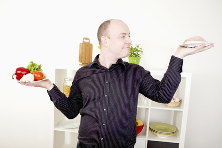 gleeful: Gleeful smiling man standing in his kitchen with his arms raised with two plates, one with fresh vegetables and one with meat, making a choice on food and diet and giving in to temptation Stock Photo