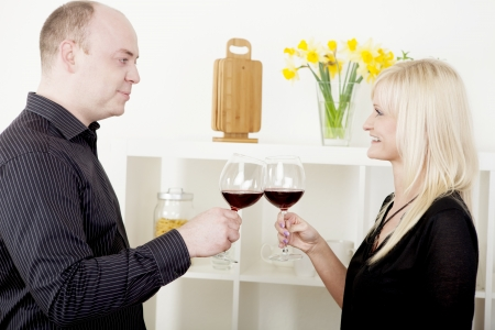 Romantic attractive man and woman standing sideways to the camera clinking their glasses of red wine in celebration toasting each other while looking into each others eyes with a smile photo