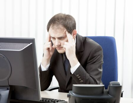 introspective: Worried businessman with a headache sitting at his desk rubbing his temples with his fingertips and staring at his desktop computer monitor in despair Stock Photo