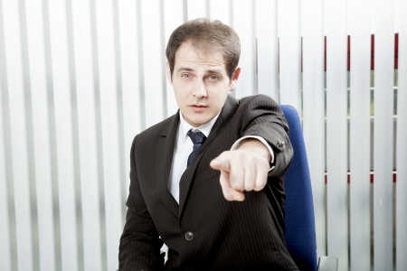 identifying: Businessman pointing a finger singling out a specific person to delegate work or to lay blame, indicating his choice or identifying somebody