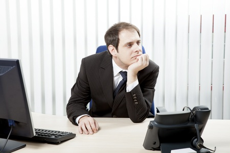 downhearted: Thoughtful businessman in his office sitting at his desk resting his chin on his hand as he stares into the distance while contemplating difficult decisions