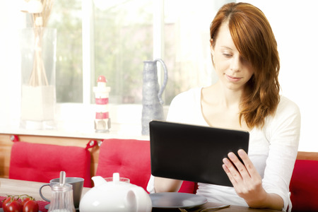 scrolling: Pretty young woman with beautiful coppery red hair sitting on a chair in the dining room browsing her tablet computer scrolling with her finger on the touchscreen Stock Photo