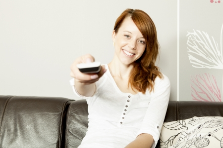unwinding: Beautiful young happy woman using a remote control pointing it at the camera as she changes a channel on the television while relaxing at home on a leather sofa
