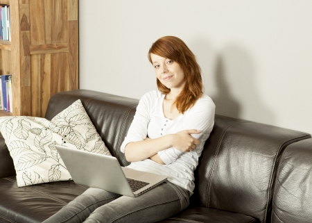 Smiling attractive young redhead woman relaxing with her laptop at home sitting on a large leather sofa, with copyspace photo