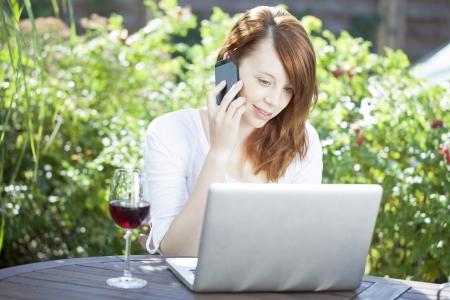 Die van huis buiten zitten aan een tafel op een tuinterras surfen op het internet tijdens het chatten op haar mobiele telefoon met een glas rode wijn naast haar