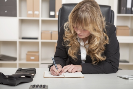Hardworking young businesswoman with land blond hair leaning over her desk in her office writing notes photo
