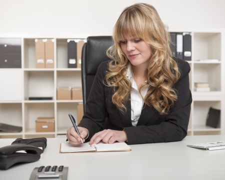 Blond businesswoman writing notes at her desk as she sits in her office with shelving lined with binders behind her photo