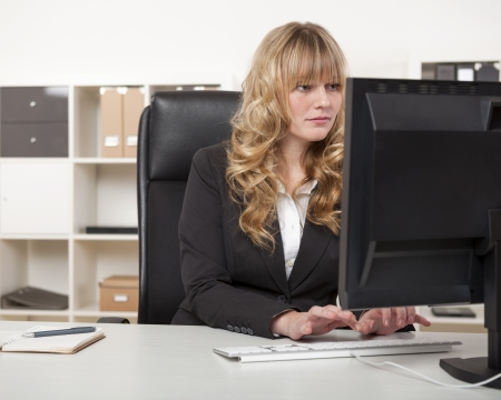Pretty blond secretary or personal assistant working at her desk in the office typing on her desktop computer photo