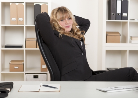 Beautiful young blond businesswoman relaxing at her desk in the office leaning back in her chair with her hands behind her head photo