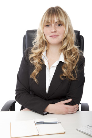 Beautiful friendly young businesswoman sitting at her desk with a notebook in front of her smiling at the camera over a white background Standard-Bild