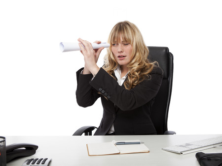 Young businesswoman spying on a colleague playfully holding a rolled up sheet of paper as a telescope to her eye photo
