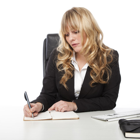 Stylish young blond businesswoman writing an appointment in her diary with a serious expression as she sits at her desk over a white background photo