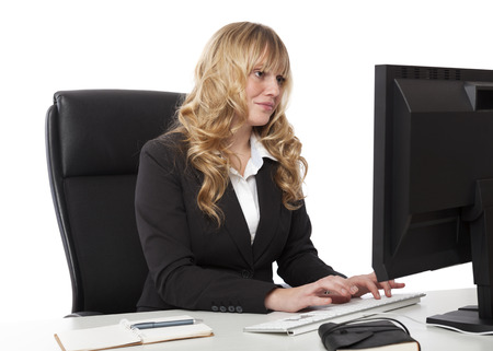 Beautiful secretary in a stylish black suit sitting typing at her desk while reading her notes on a desktop monitor photo