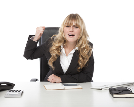 Businesswoman raising her fist in frustration while yelling out as she voices her displeasure while seated at her desk in the office photo