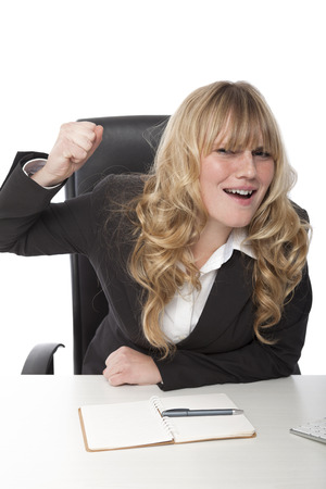 Beautiful young businesswoman with lovely long wavy blond hair raising her fist in the air photo