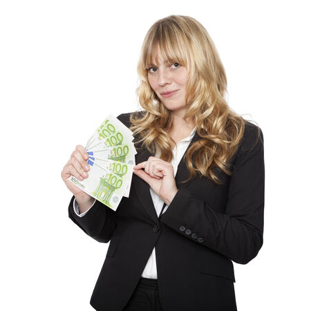 conspiratorial: Young businesswoman with a handful of 100 euro notes tweaking one with her finger as she looks at the camera with a pleased conspiratorial smile isolated on white