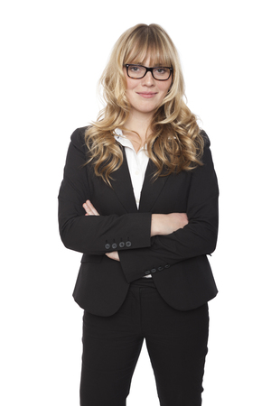 Confident friendly businesswoman with long wavy blond hair wearing glasses and a slacksuit standing smiling at the camera with folded arms, on white Standard-Bild
