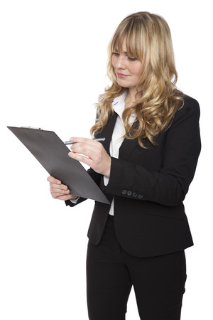 customer records: Beautiful young businesswoman standing writing notes on a handheld clipboard as she conducts a survey a quality control isolated on white