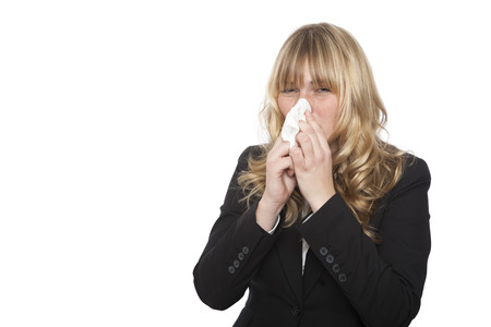 Businesswoman suffering with a seasonal winter cold or the flu blowing her nose on a tissue in an effort not to spread her germs, isolated on white Standard-Bild